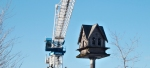 crane looming over birdhouse