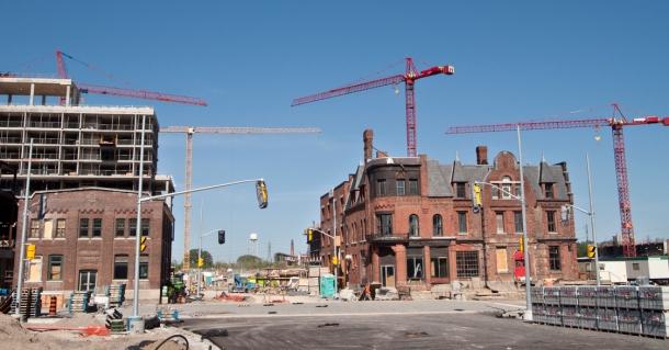 Cranes surrounding old brick building.