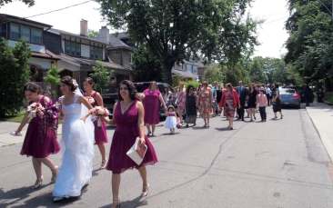Bridal party walking down the middle of the street.