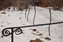 Handrail beside snowy path.