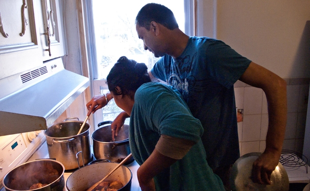 Couple stirring food in pots on stove.