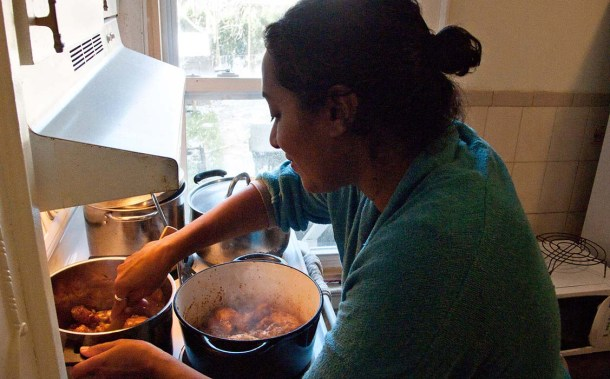 A woman frying chicken.