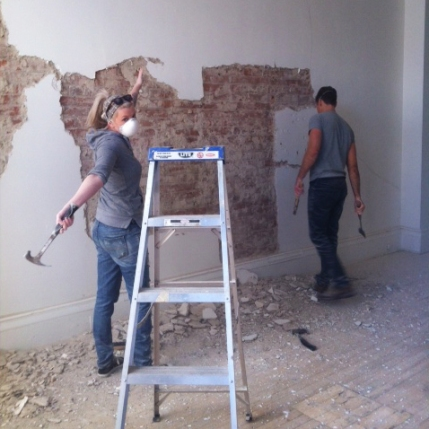 Workers removing plaster from brick walls at Boxcar Social.