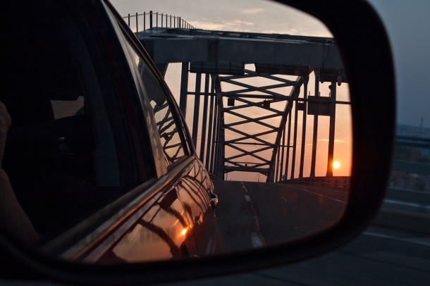 View of bridge and setting sun through rear view mirror.