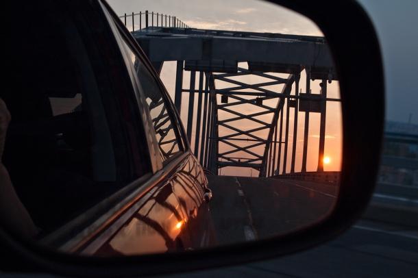 View of bridge and setting sun through rear view mirror.