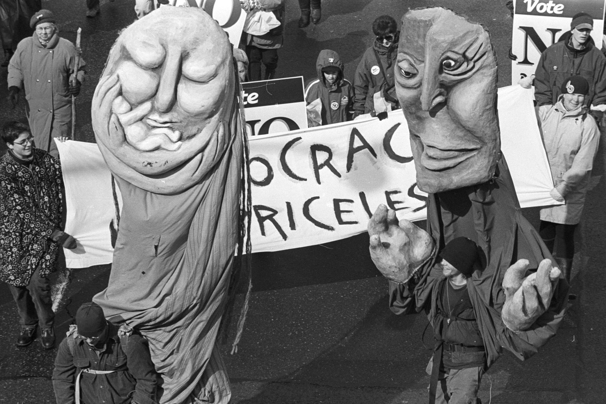 Giant puppets march against the megacity.