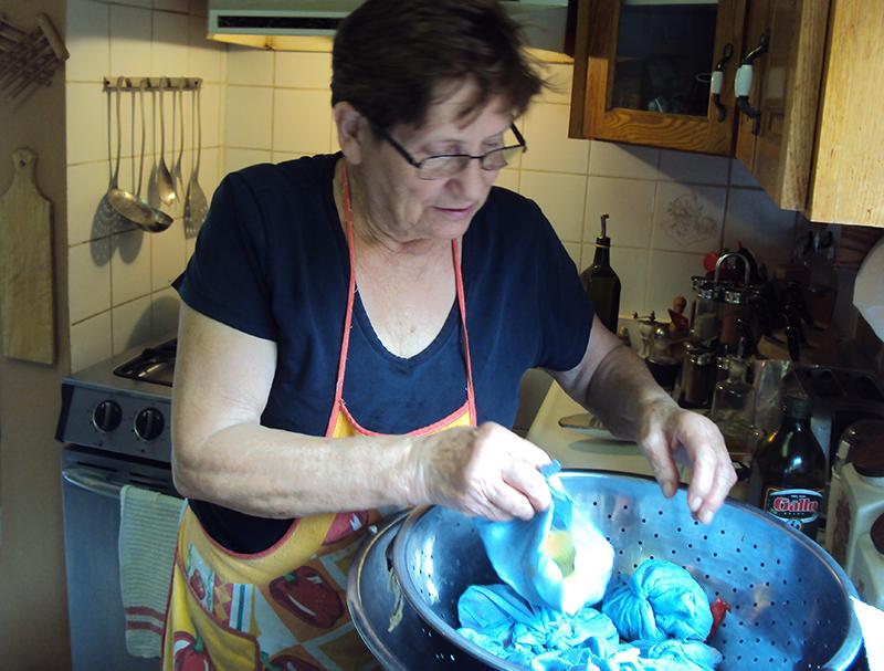 Mother placing vegetables in colander.