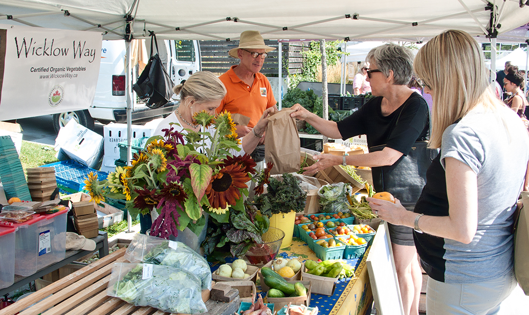 Farmers at market with flowers.