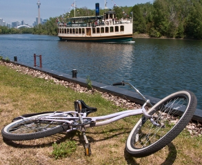Bike beside island channel with boat.