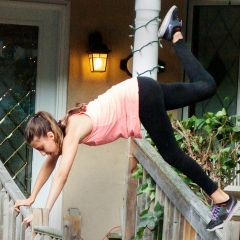 Girl dancing on porch railing.