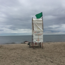 Lifeguard stand with green flag.