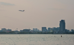 Plane taking off over swimmers at Hanlan's.
