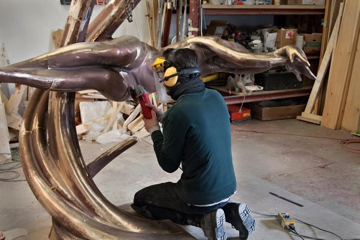 Grinding joins on bronze sculpture.