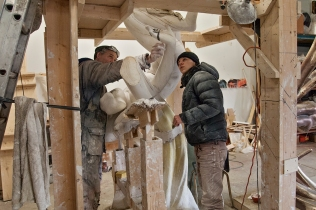 Sculptor showing assistant a point.