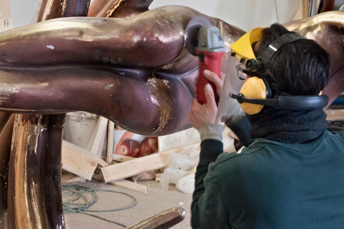 Grinding welds on sculpture.