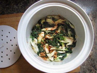 Sauce mixed into bok choy in kimchi preparation.