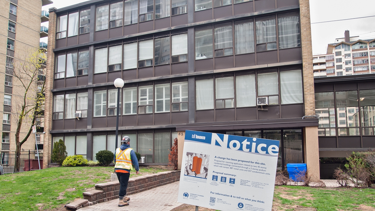 Lowrise apartment building with redevelopment notice.