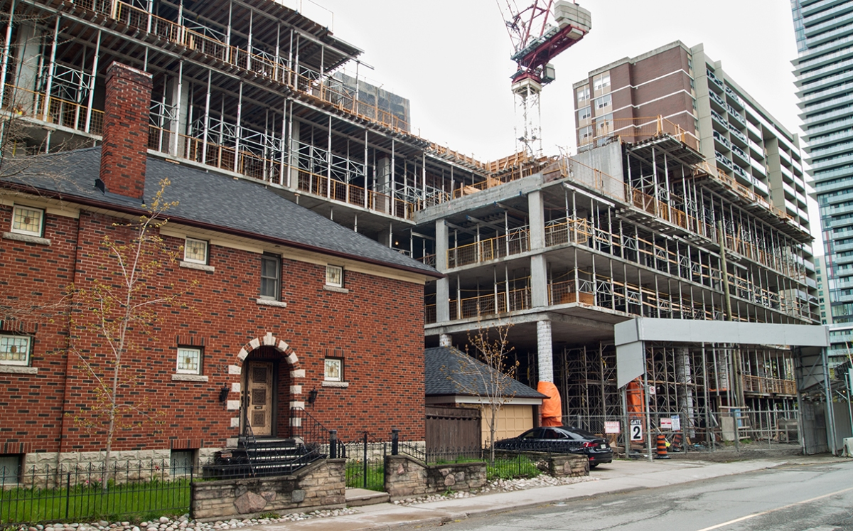 Old brick house surrounded by apartment construction.
