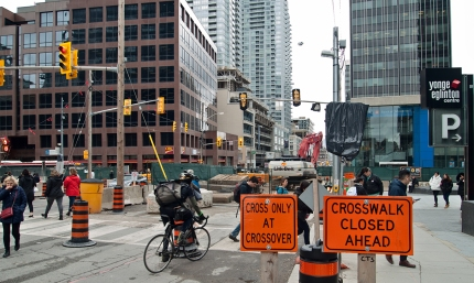 Construction signs and barriers at intersection.
