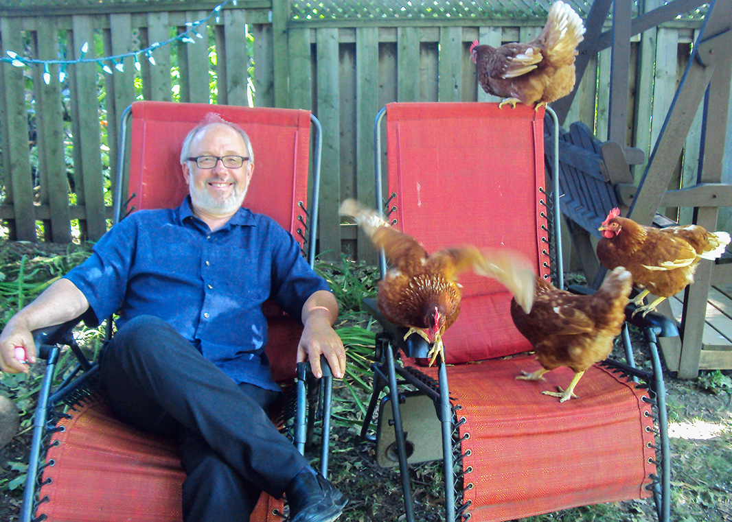 Joe Mihevc and chickens sitting in lawn chairs.